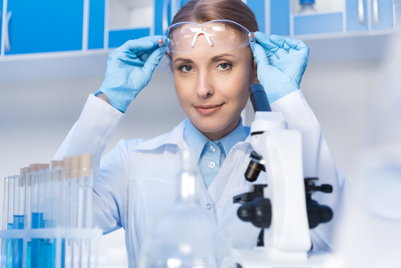 scientist with microscope looking at camera